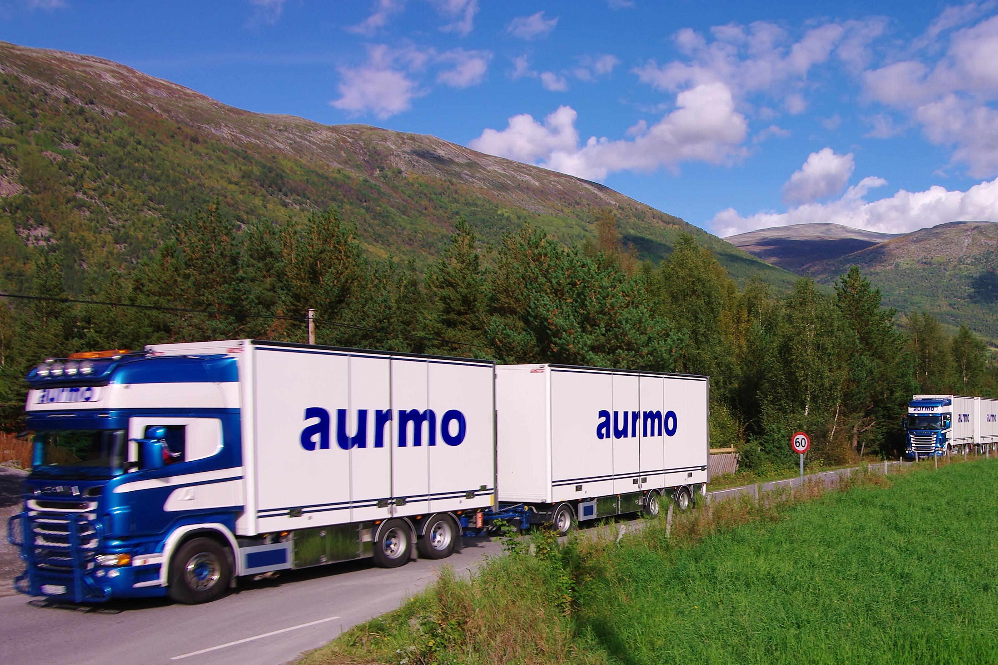 Bilde av transportfirmaet Aurmo Transport sine biler som kjører på en norsk vei.